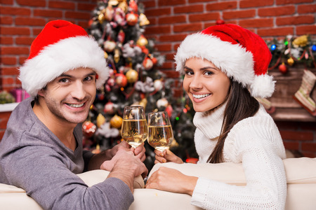 Enjoying Christmas time together. Happy young loving couple in Santa hats looking over shoulders and smiling while sitting on the couch together and drinking wine with Christmas Tree in the background photo