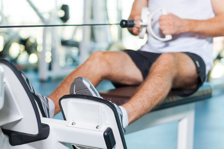 fit body: Sports training. Close-up of young man working out in gym