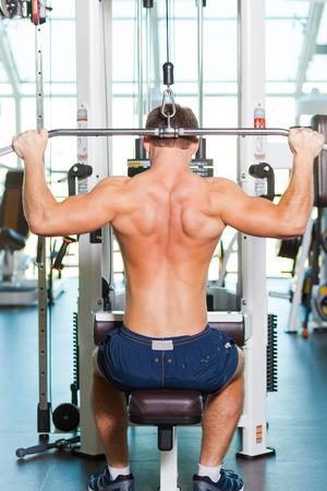 only the biceps: Training his body to perfection. Rear view of young muscular man working out on bench press Stock Photo
