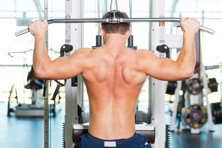 weightlifting equipment: Staying in perfect form. Rear view of young muscular man working out on bench press