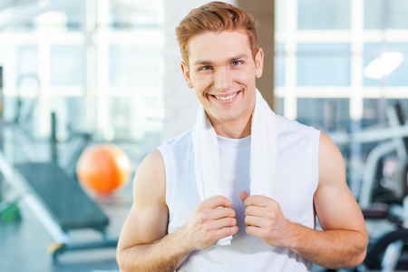 only the biceps: Strong and confident. Confident young muscular man carrying towel on shoulders and smiling while standing in gym