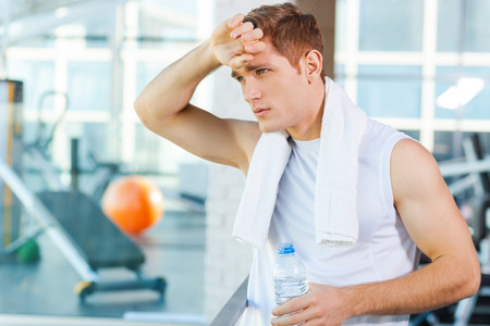 tired: Resting after work out. Tired young man carrying towel on shoulders and touching his forehead while standing in gym