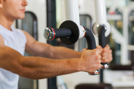 Sports training in gym. Concentrated young and sporty man working out in gym Stock Photo