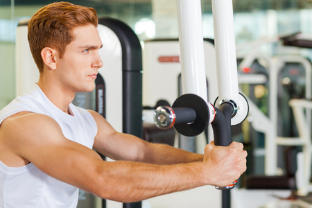 staying in shape: Staying in shape is very important. Concentrated young and sporty man working out in gym Stock Photo