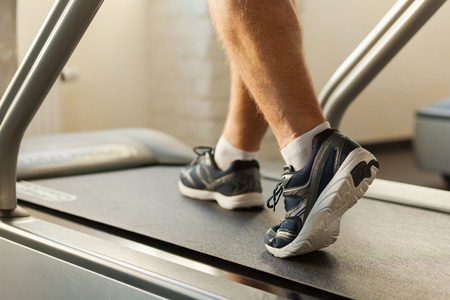 recreational pursuits: Exercising on treadmill. Close-up of man walking by treadmill in sports club