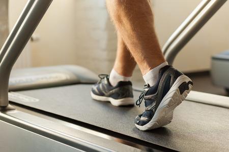 personas corriendo: Hacer ejercicio en cinta rodante. Primer plano de hombre caminando por la cinta en el club deportivo