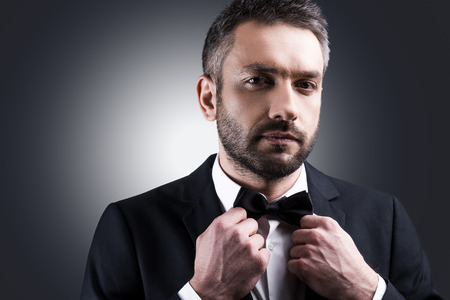 evening class: Used to look perfect. Portrait of handsome mature man in formalwear adjusting his bow tie and looking at camera while standing against grey background