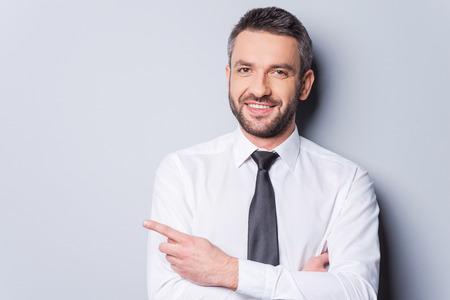 Wijzend uw product. Portret van knappe volwassen man in overhemd en das niet goed kopie ruimte en glimlachen terwijl staande tegen een grijze achtergrond Stockfoto
