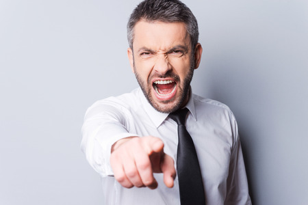 angry businessman: It is your fault! Furious mature man in shirt and tie shouting and pointing you while standing against grey background Stock Photo