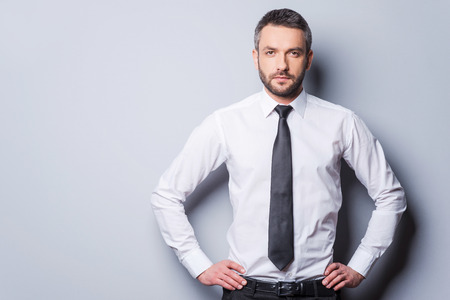 human hip: Confident and successful. Confident mature man in shirt and tie holding hands on hip and looking at camera while standing against grey background Stock Photo