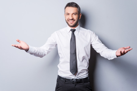 hair tie: You are welcome! Cheerful mature man in shirt and tie gesturing welcome sign and smiling while standing against grey background Stock Photo