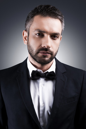 evening class: Classy handsome. Portrait of handsome mature man in formalwear and bow tie looking at camera while standing against grey background