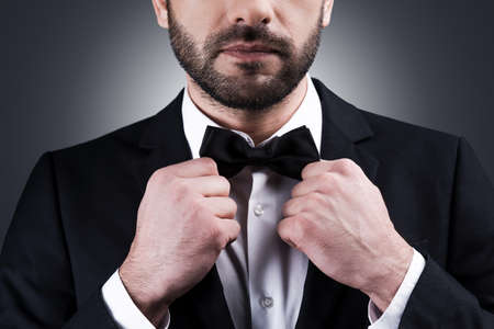 Perfect style. Close-up of handsome mature man in formalwear adjusting his bow tie while standing against grey background Stock Photo