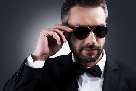 heartbreaker: Confident heartbreaker. Portrait of handsome mature man in formalwear adjusting his sunglasses while standing against grey background
