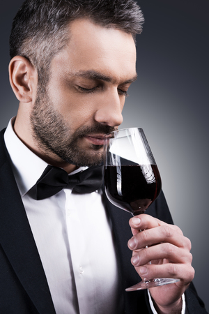 closed society: Perfect wine. Portrait of handsome mature man in formalwear smelling red wine in his glass and keeping eyes closed while standing against grey background