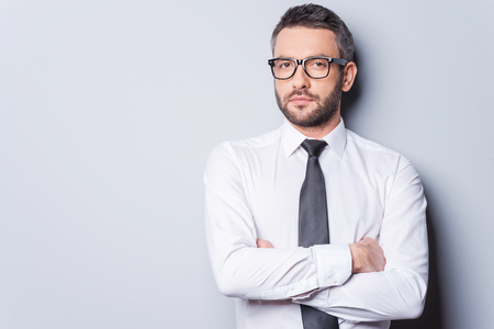 hair tie: Portrait of confidence and success. Portrait of handsome mature man in shirt and tie keeping arms crossed and looking at camera while standing against grey background