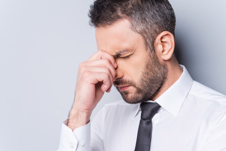 human nose: Depressed businessman. Portrait of frustrated mature man in shirt and tie touching his nose and keeping eyes closed while standing against grey background Stock Photo