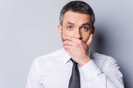 only one man: I am shocked! Surprised mature man in shirt and tie covering mouth with hand and looking at camera while standing against grey background Stock Photo