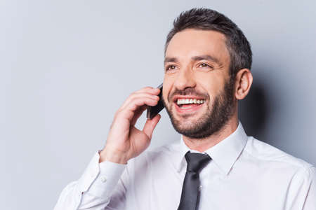 stubble: Great news! Happy mature man in shirt and tie talking on the mobile phone and smiling while standing against grey background