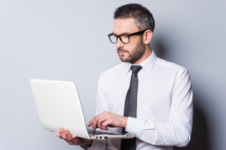business person: Business expert at work. Confident mature man in shirt and tie working on laptop while standing against grey background Stock Photo