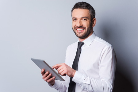 Feeling satisfied with his new gadget. Confident mature man in shirt and tie working on digital tablet and smiling while standing against grey background Stock fotó