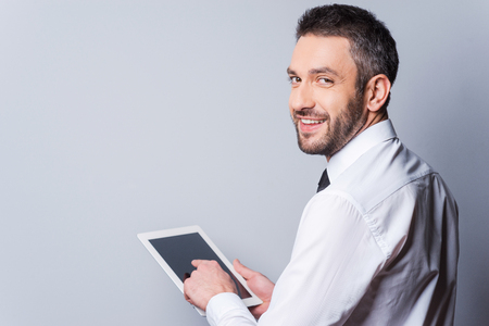 Man with digital tablet. Rear view of happy mature man in shirt and tie working on digital tablet and looking over shoulder while standing against grey background photo