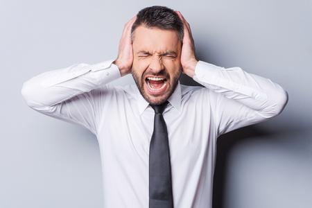 boca cerrada: Estoy harto de él! Hombre maduro furioso en camisa y corbata y gritando que cubre los oídos con las manos mientras está de pie contra el fondo gris Foto de archivo