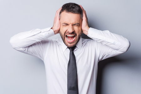mouth closed: I am fed up with it! Furious mature man in shirt and tie shouting and covering ears with hands while standing against grey background