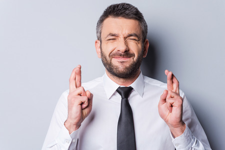 특별한 것을 기다리는 중입니다. 회색 배경에 서있는 동안 셔츠와 넥타이 손가락을 유지하고 성숙한 남자는 눈을 감았 다. 스톡 콘텐츠 - 34400634
