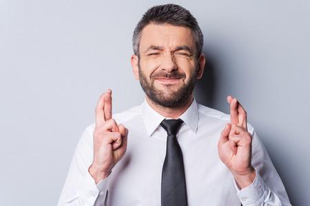 Wachten op iets bijzonders. Volwassen man in overhemd en stropdas houden de vingers gekruist en de ogen gesloten terwijl je tegen een grijze achtergrond