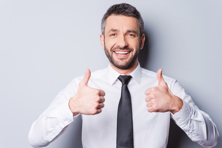 Thumbs up for success! Happy mature man in shirt and tie showing his thumbs up and smiling while standing against grey background Stok Fotoğraf