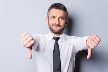 office attire: Bad news for you! Mature man in shirt and tie showing his thumbs down while standing against grey background Stock Photo