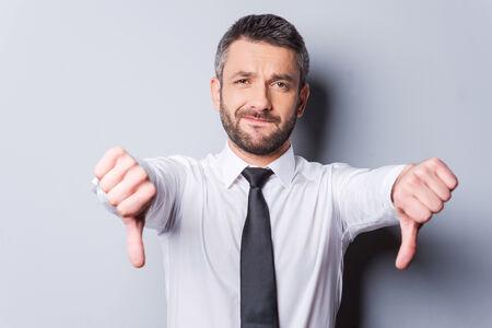 empleado de oficina: Malas noticias para usted! Hombre maduro en camisa y corbata mostrando sus pulgares hacia abajo mientras est� de pie contra el fondo gris