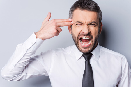 I am fed up with it! Furious mature man in shirt and tie gesturing handgun near head and shouting while standing against grey background photo