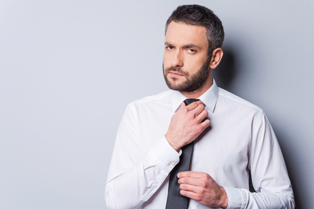 adjusting: Ready to business meeting. Confident mature man adjusting his necktie and looking at camera while standing against grey background