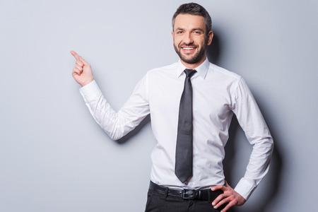 Kopieer ruimte naar zijn hand. Gelukkig volwassen man in overhemd en stropdas wijst kopie ruimte en glimlachen terwijl staande tegen de grijze achtergrond