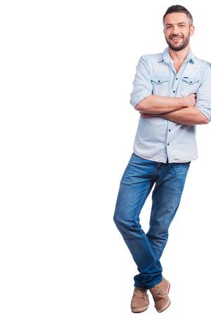Lässig schön. In voller Länge von schönen jungen Mann in Freizeitkleidung gelehnt auf Kopie Raum und lächelnd im Stehen vor weißem Hintergrund