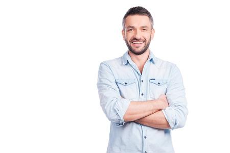 weiß: Charmante hübscher. Gut aussehender junger Mann in Freizeitkleidung hält Armen und lächelnd im Stehen isoliert auf weißem Hintergrund