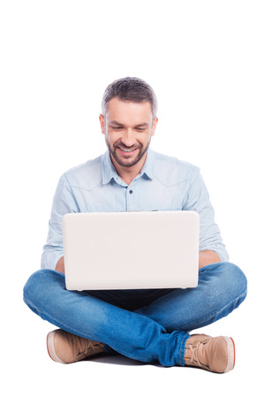 surfing the net: Man surfing the net. Handsome young man in casual wear sitting on the floor and working on laptop while being isolated on white background Stock Photo