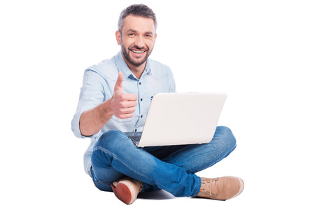 Technologies become easier! Handsome young man in casual wear sitting on the floor with laptop and showing his thumb up while being isolated on white background photo