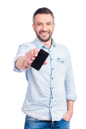 Showing his brand new smart phone. Handsome young man in casual wear showing his smart phone and smiling while standing isolated on white background photo