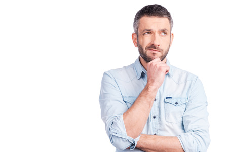 Feeling uncertain about?Frustrated young man in casual wear holding hand on chin and looking away while standing isolated on white background 스톡 콘텐츠
