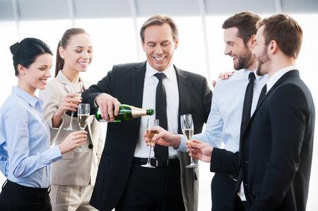 jovenes tomando alcohol: Celebrar el �xito. Grupo de hombres de negocios la celebraci�n de flautas con champ�n y sonriente mientras est� de pie cerca uno del otro en el interior Foto de archivo