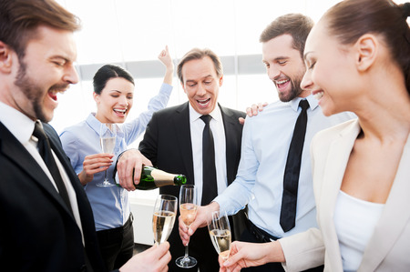 deserve: We absolutely deserve this! Group of happy business people holding flutes while mature man pouring champagne