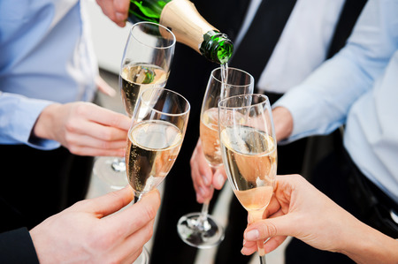 great success: Celebrating great success. Close-up of business people holding flutes with champagne and toasting