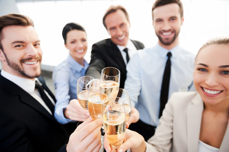 business person: Toasting to success. Group of business people toasting with champagne and smiling while standing close to each