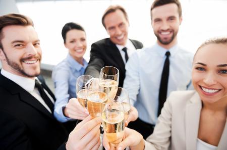 jovenes tomando alcohol: Tostar al �xito. Grupo de personas de negocios brindando con champ�n y sonriendo mientras est� de pie cerca uno