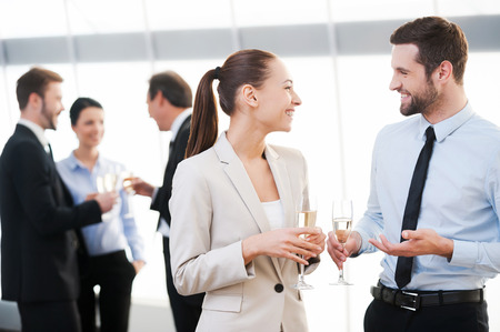 business person: Celebrating their common success. Two cheerful business people drinking champagne and talking while other people communicating in the background