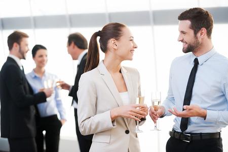 Vieren hun gemeenschappelijke succes. Twee vrolijke mensen uit het bedrijfsleven drinken champagne en praten, terwijl andere mensen communiceren in de achtergrond