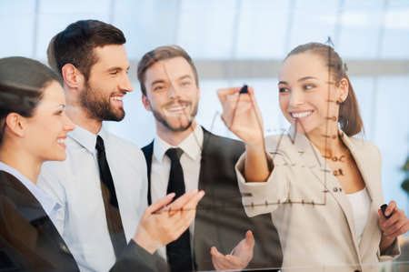 business person: Discussing successful business project. Confident young businesswoman drawing a graph on glass and smiling while her colleagues standing near her